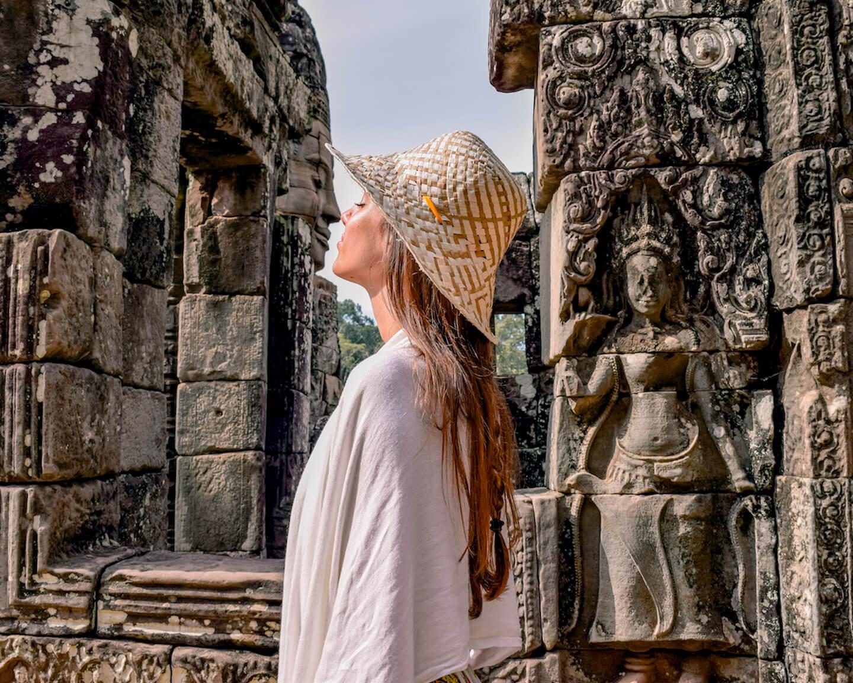 Chica fingiendo besar la cara de piedra en las ruinas del templo