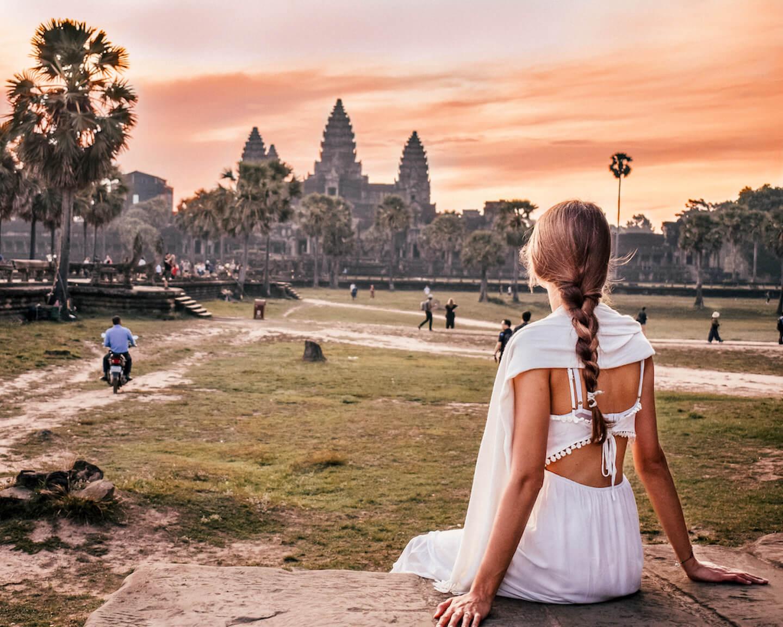 niña mirando el amanecer detrás del templo de angkor wat